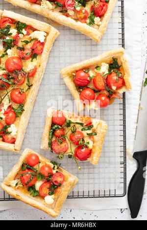 La tomate, basilic et boccocini tartelettes avec couper des morceaux sur une grille. Banque D'Images