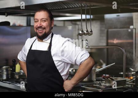 Concept alimentaire. Un jeune cuisinier se tient dans la cuisine. Banque D'Images