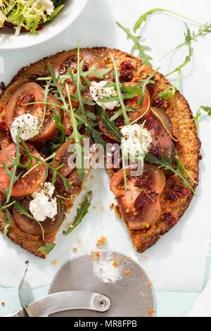 Le quinoa sain pizza avec des tomates, des tomates séchées, fromage de chèvre et de feuilles de roquette