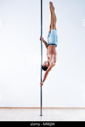 Les jeunes pole dancing man on white wall background Banque D'Images