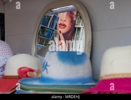 Visage de femme sur la publicité reflète dans un miroir à un blocage dans le port de Kyrenia hat le nord de Chypre. Banque D'Images
