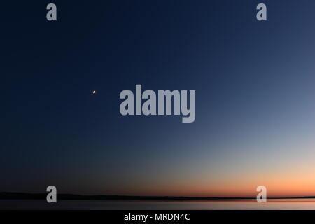 La lune de la lune dans le ciel bleu nuit noire au-dessus du lac Banque D'Images