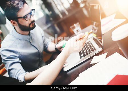 Jeune homme barbu dans les verres analyse le travail d'équipe fait. Travaille au bureau avec un ordinateur portable et d'accessoires de bureau. Arrière-plan flou Banque D'Images