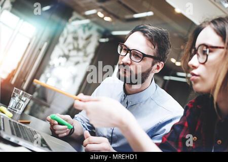 Homme d'équipe de travail sur un nouveau concept derrière un ordinateur portable moderne en open space office. Arrière-plan flou. Démarrage d'une nouvelle réflexion