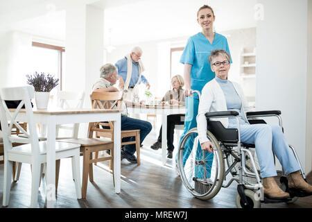 Senior woman in wheelchair with care worker en maison de soins.