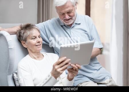 Senior couple in hospital room looking at digital tablet. Banque D'Images