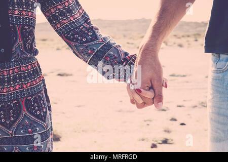 Close up of paire de mains ensemble touchant la tenue pour du vrai vrai amour entre homme et femme caucasienne. jeunes voyageur en vacances avec plage gam Banque D'Images