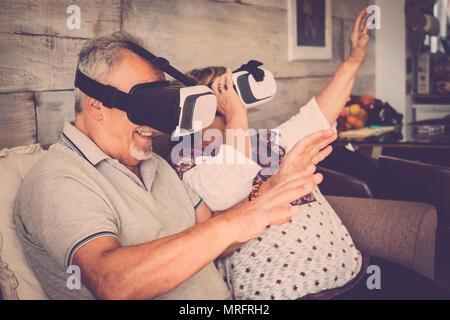 Hauts homme et femme avec casque lunettes lunettes de réalité virtuelle et d'avoir du plaisir à jouer assis sur le canapé à la maison. Filtre chaud et vie ensemble c Banque D'Images
