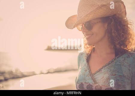 Belle et grande blonde les cheveux bouclés d'âge moyen modèle chapeau de cow-boy avec sourire et poser à la plage avec coucher du soleil doré à l'arrière-plan. une couleur