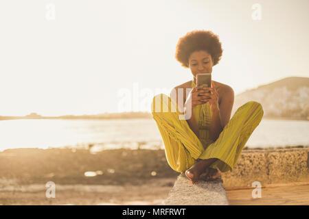 Belle race noir modèle africain avec des cheveux bien utiliser le smartphone s'asseoir près de l'océan et la plage de liberté en vacances activité. conta Banque D'Images