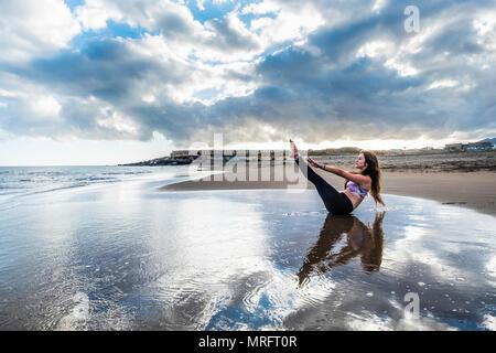Fitness Pilates ont les soins du corps et la position de repos séjour pour les jeunes caucasian woman sur le rivage à la plage. scenic image pour la santé du corps concept. yo Banque D'Images