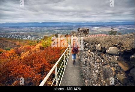 Femme de tourisme à chapeau brun sac à dos et marcher sur l'ancienne muraille de la ville avec vue d'Alazani valley à l'automne dans le temps, la Géorgie Sighnaghi Banque D'Images
