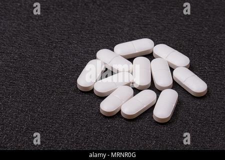 Close up pilules blanches sur fond noir. Banque D'Images