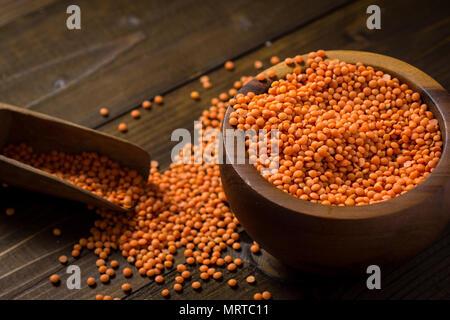 Les lentilles rouges Bio sain dans un bol sur la table en bois foncé Banque D'Images