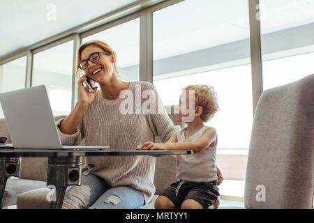 Petit garçon assis avec sa mère talking on cell phone. Femme occupée avec fils en home office. Banque D'Images