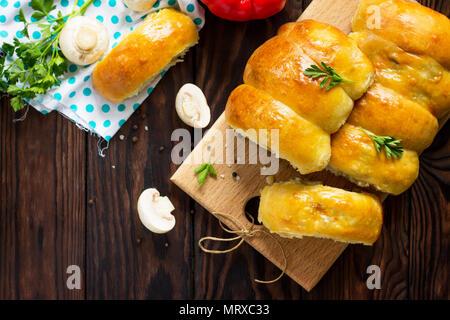 Tartes aux champignons et du riz sur la table en bois de cuisine. La cuisine russe traditionnelle. Banque D'Images