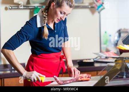 Coupe femme boucher morceau de viande de côtes dans sa boutique Banque D'Images