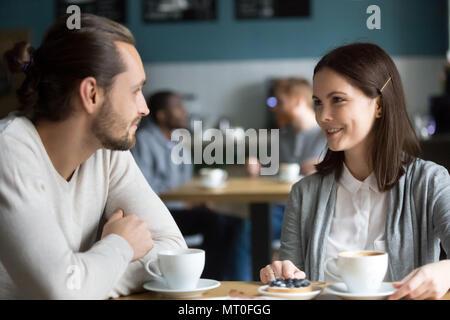 Heureux couple millénaire dans aime parler flirting at cafe table Banque D'Images
