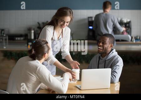 Serveuse et multiraciale visiteurs riant de plaisanterie drôle in cafe Banque D'Images
