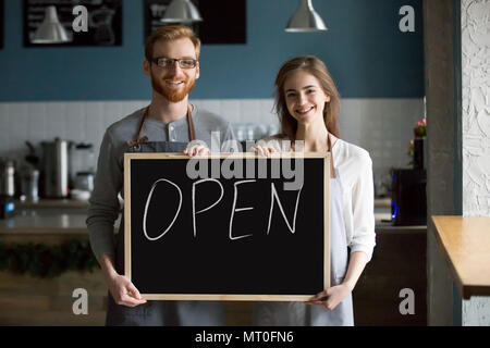 Smiling waiter et waitress holding chalkboard with open sign, p Banque D'Images