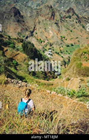 Hiker femme prendre un repos sur la pente de montagne. Assis sur un sommet et profiter d'une vue spectaculaire. Paysage coloré. Matin lumineux et de la lumière du soleil dans la vallée de Coculi sur Santo Antao Cape Verde Banque D'Images