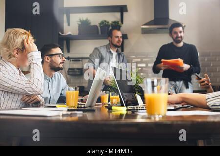 Groupe de collaborateurs créatifs au brainstorming cuisine. Les gens d'affaires et travailler ensemble à l'aide d'ordinateurs portables. Jeune équipe de gestionnaires de grandes entreprises Banque D'Images
