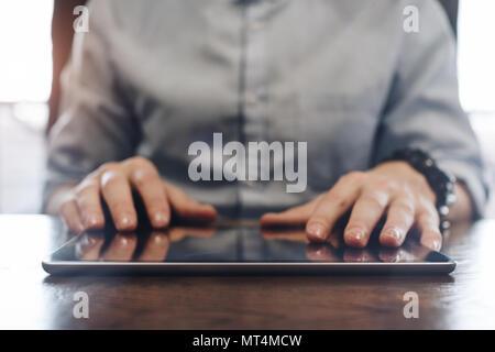 Gestionnaire de compte et de la saisie sur tablette moderne. Tablet close up sur un bureau en bois dans un bureau. Men's hands touching screen tablet Banque D'Images