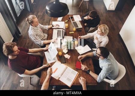 Groupe de collaborateurs créatifs s'asseoir autour d'une table en bois dans un espace ouvert et travaille avec les entreprises la documentation et les ordinateurs portables. Concept de travail dans l'Offic Banque D'Images
