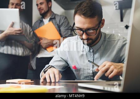 Homme barbu à lunettes utilise un ordinateur tablette. D'équipe sur un nouveau démarrage. Les analystes d'affaires. Dans un loft moderne coworking space using electronic Banque D'Images