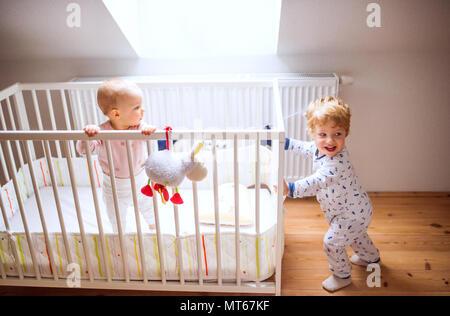 Deux enfants dans la chambre des tout-petits à la maison. Banque D'Images