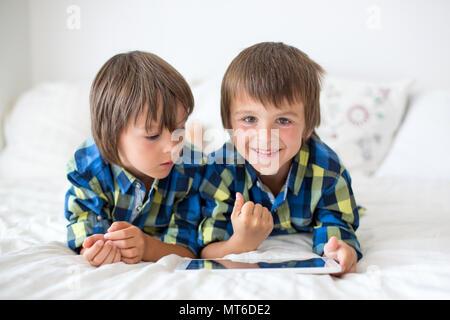 Deux enfants d'âge préscolaire, garçon frères, jouant à la maison au lit sur tablette Banque D'Images