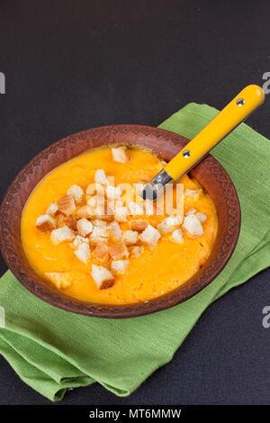 Soupe de carottes et de potiron à la crème et le persil sur fond sombre Banque D'Images