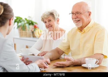 Smiling senior homme et femme de parler à un conseiller financier au sujet d'un prêt Banque D'Images