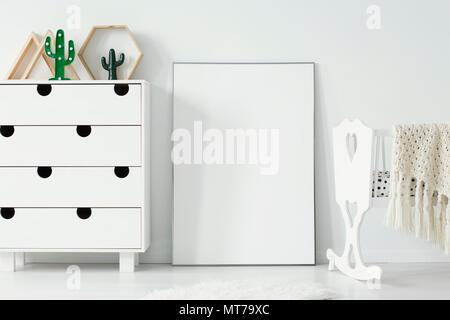 Affiche blanche vide avec immersive entre le meuble et le berceau dans la chambre de bébé l'intérieur. Photo réelle. Placez votre design graphique ici