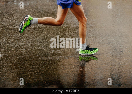 Athlète jambes runner fonctionnant sur l'asphalte mouillé de la pluie gray Banque D'Images