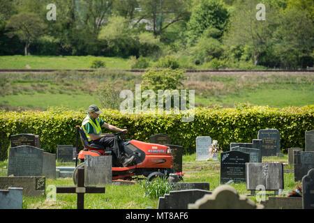 Homme au travail (empoyee de conseil local) siège au tour sur tondeuse et coupe de l'herbe entre les pierres tombales du cimetière - Guiseley, West Yorkshire, Angleterre, Royaume-Uni. Banque D'Images