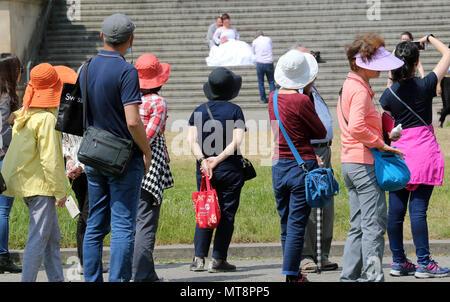 28 mai 2018, l'Allemagne, Berlin: un groupe de touristes en provenance de la Corée dans le Lustgarten observe un couple de poser pour des photos sur les marches de l'Altes Museum. Photo: Wolfgang Kumm/dpa Banque D'Images