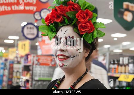 Une jeune femme dans un magasin avec son visage peint et une coiffe de roses rouges pour la parade annuelle dans la région de Barnard Castle, Angleterre, RU Banque D'Images