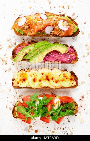 Assortiment de toasts déjeuner sain entouré par les miettes et les graines sur un fond rustique blanc. Haut de la vue, télévision lay Banque D'Images