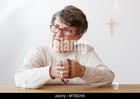 Vieille dame à lunettes assis à la chapelle et priant avec rosaire Banque D'Images