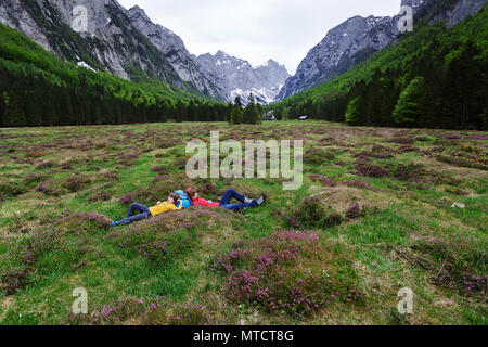 Mère et fils couché sur l'herbe dans la vallée pittoresque entre montagnes, Vallée Krma, la Slovénie. Banque D'Images