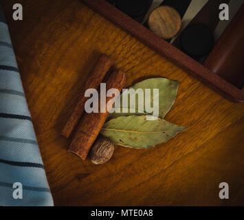 La cannelle, la muscade et le laurier reposant sur une table en bois dans un cadre rustique Banque D'Images