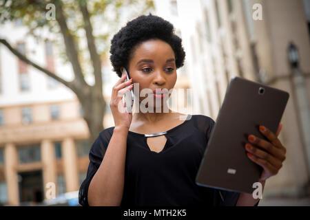 Business Woman talking on cell phone et la lecture d'un comprimé Banque D'Images