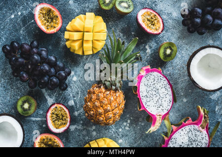 Les fruits tropicaux, les fruits exotiques sur fond de béton. Mise à plat de fruits. Dragonfruit, fruit de la passion, noix de coco, mangue, kiwi et raisin. Fresh fruit cru bac Banque D'Images
