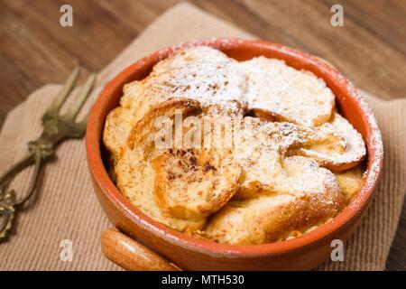 Pot en terre cuite de pain et beurre au lait partiellement couvert par du sucre en poudre Banque D'Images