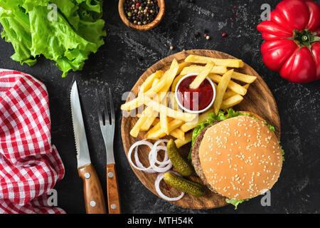 Burger de boeuf avec de la laitue et la tomate, la pomme de terre frites et ketchup sur fond sombre. Vue de dessus de table. Restauration rapide, une mauvaise alimentation concept Banque D'Images
