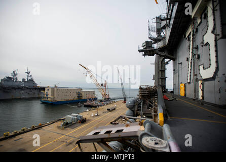 170105-N-RT036-069 NORFOLK (janv. 5, 2017) une installation d'hébergement flottant (FAF) arrive aux côtés du porte-avions USS George Washington (CVN 73). La FAF fournira de l'équipage de George Washington à des services médicaux et dentaires, ainsi qu'une cuisine et de quartiers pour le personnel de service pendant que le navire est soumis à l'entretien. George Washington est homeported à Norfolk se préparent à partir à Newport News, Virginie pour le ravitaillement du navire révision complexe (RCOH) maintenance. (U.S. Photo par marine Spécialiste de la communication de masse 2e classe Jessica Gomez/libérés) Banque D'Images
