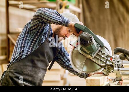 Carpenter travailler avec une scie circulaire pour les planches à découper, l'homme découpe des bars, de la construction et de la rénovation domiciliaire, la réparation et l'outil de construction Banque D'Images