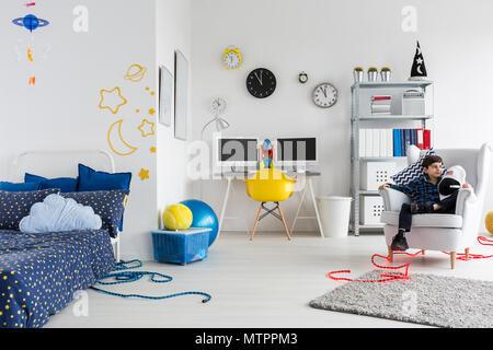 Prise d'un petit garçon assis dans un fauteuil dans sa chambre sur le thème de l'espace Banque D'Images
