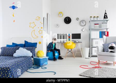 Prise d'un petit garçon dans sa chambre sur le thème de l'espace Banque D'Images